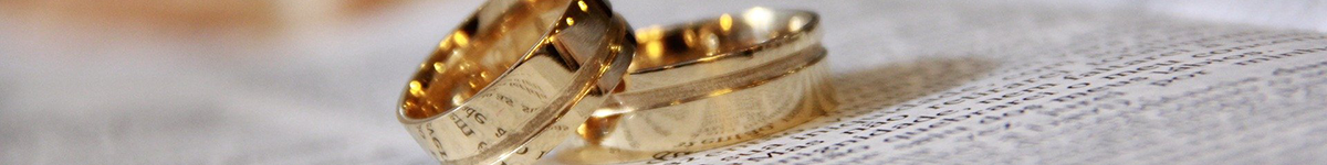 A pair of wedding bands lie on an open book