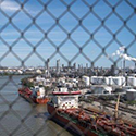 view of ships in port through chain-link fence
