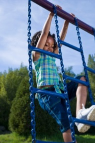 Young girl on jungle gym ladder